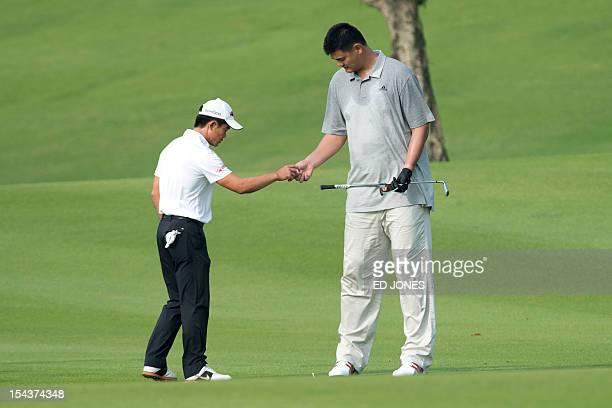 Basketball player Yao Ming of China takes a ball from Liang WenChong of China during the Mission Hills World Celebrity ProAm golf event at the...