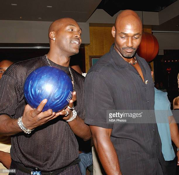 Basketball players Bryon Russell and Karl Malone get ready to bowl at a party held for Gary Payton and Karl Malone celebrating both Los Angeles...