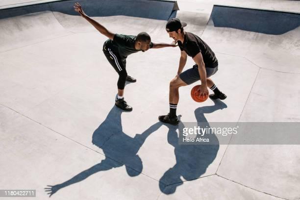 Basketball players dribbling and defending