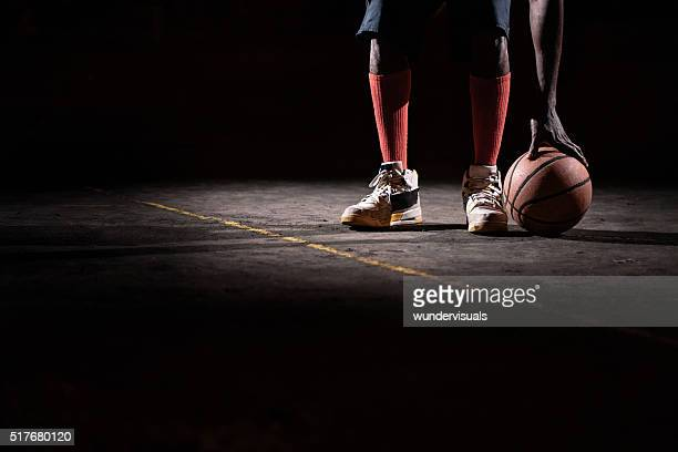 Basketball Players Feet and hand on ball, court ground