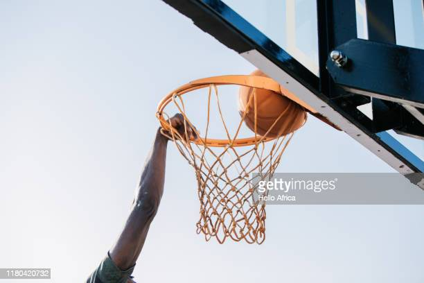 A basketball player's hand grips the edge of the hoop he scores