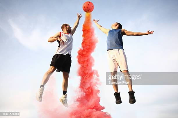 Basketball players jumping to smoking ball