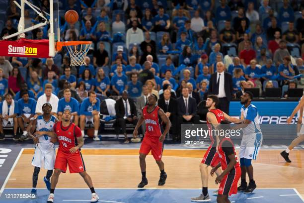 basketball players looking at ball reaching to hoop - basketball competition stock pictures, royalty-free photos & images