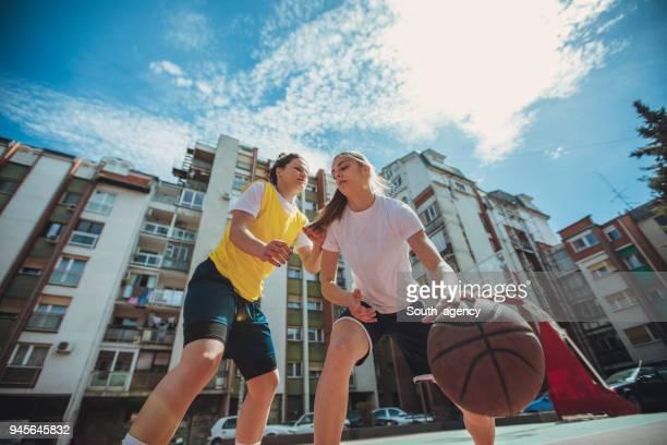 Basketball-Spieler spielen Basketball auf dem Spielplatz