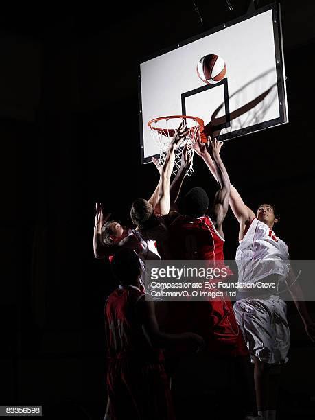 basketball players reaching for the ball - basketball team stock pictures, royalty-free photos & images
