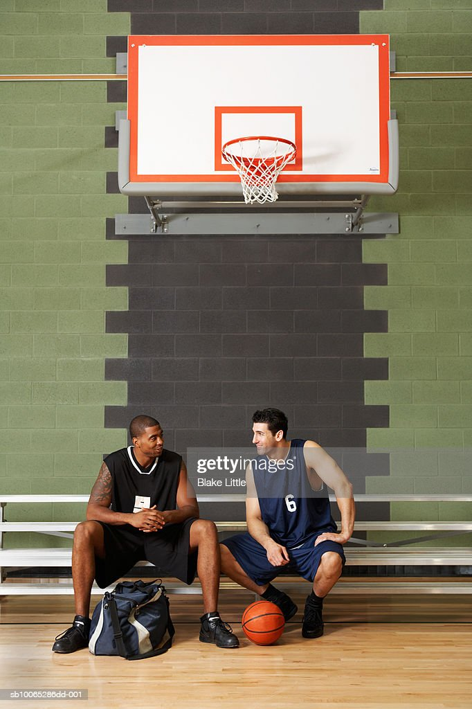 Basketball players sitting on bench under basketball ring : Foto stock