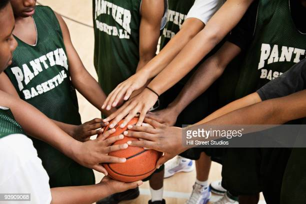 basketball players touching ball in huddle - basketball team stock pictures, royalty-free photos & images