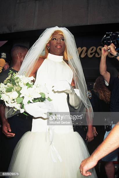 Basketball star and actor Dennis Rodman, dressed as a bride, is surrounded by photographers in Rockefeller Center.