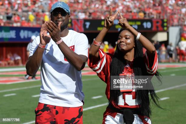 Basketball star Dwyane Wade and actress Gabrielle Union greet fans during a break in the game between the Nebraska Cornhuskers and the Rutgers...