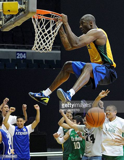Basketball star Kobe Bryant hangs on the rim as he dunks the ball while playing with collage students during a friendly game in Manila on July 13,...