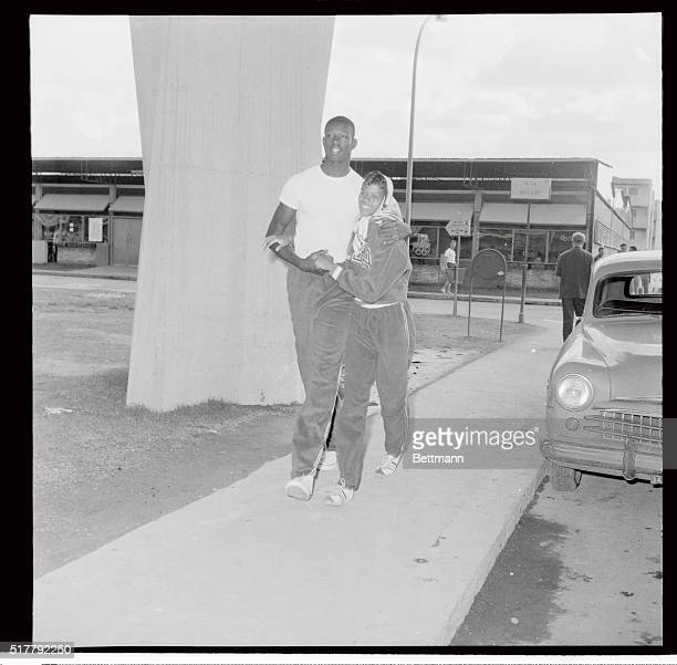 US Basketball star Walt Bellamy six feet 11 inches tall hugs American sprint star Wilma Rudolph during a stroll through the Olympic Village here...