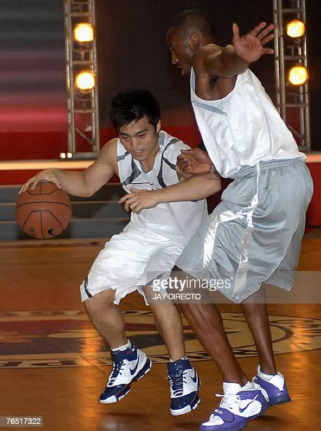 NBA basketball superstar Kobe Bryant of the Los Angeles Lakers plays with Mike Gamboa a student of the University of the Philippines during a...