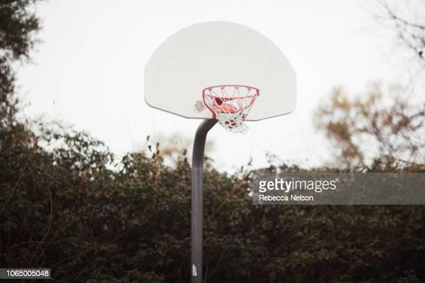 Basketball swishing through basketball hoop's net