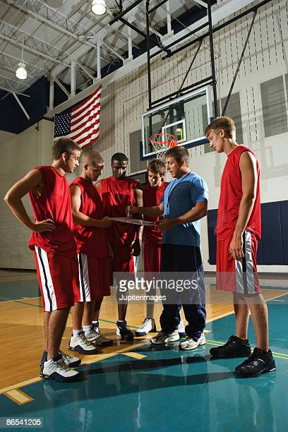 Basketball team and coach on court