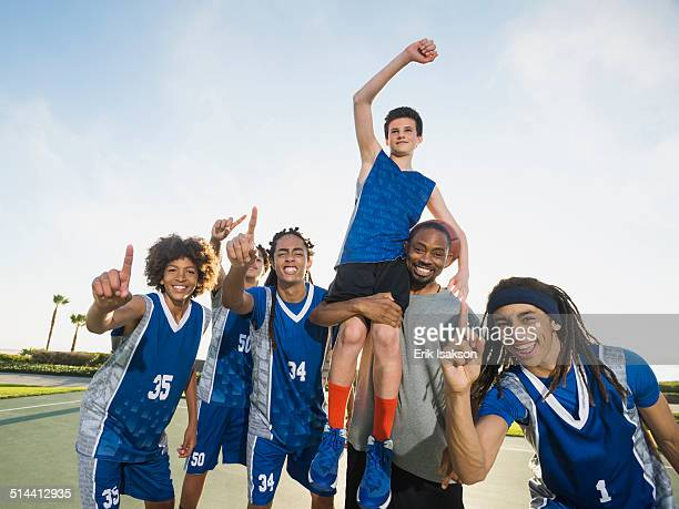 Basketball team cheering on court