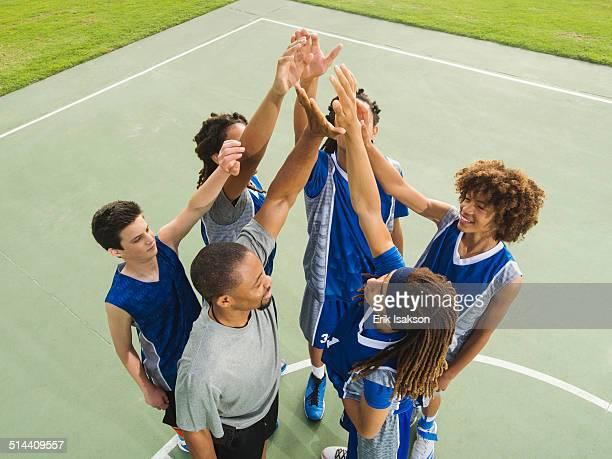 Basketball team high fiving on court