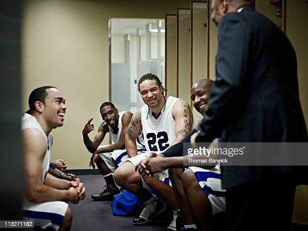 basketball team in locker room with coach - basketball team stock pictures, royalty-free photos & images