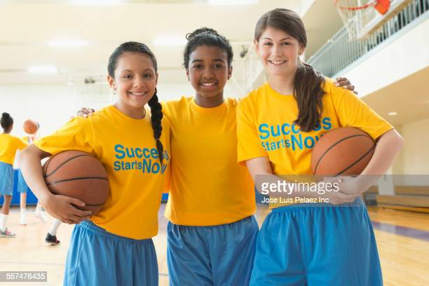 Basketball team smiling in gym