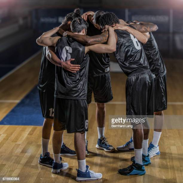 basketball team standing in cirlcle - freundschaft stockfoto's en -beelden
