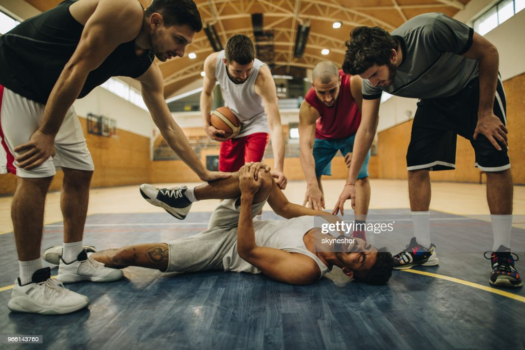 Basketball team supporting their injured teammate on the court. : Stock Photo