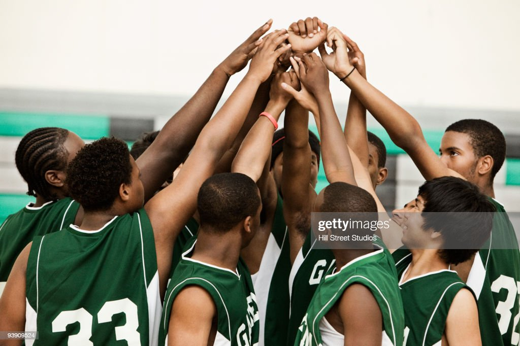 Basketball team with arms raised in huddle : Stock Photo