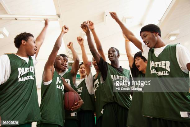 Basketball team with arms raised