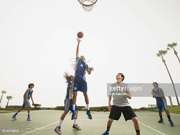 basketball teams playing on court - taking a shot sport stock pictures, royalty-free photos & images