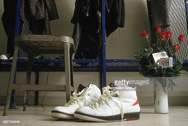 View of Nike Air Jordan II sneakers of Chicago Bulls Michael Jordan with roses on floor of locker room before game vs Detroit Pistons at Pontiac...
