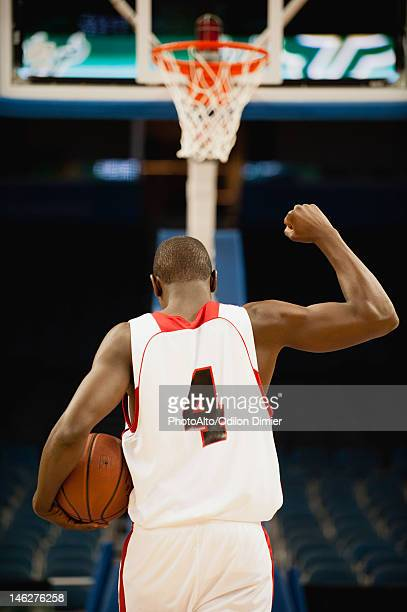 Basketball with fist raised in victory, rear view