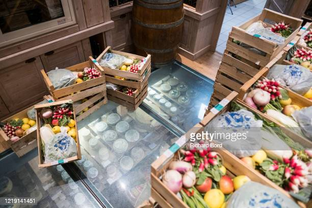 Baskets of fresh vegetables and fruits from 'Le Col Fleuri' farm are seen in Pierre Gay's shop on April 16, 2020 in Annecy, France. During the...