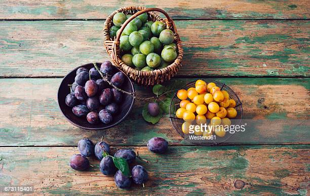 Baskets of plums, mirabelles and greengages on wood