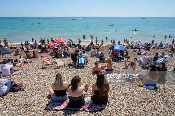 Basking in the sunshine on Brighton beach as thousands flock to the seaside to make the best of the Bank Holiday sunshine and celebrate the easing of...