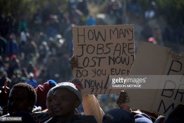 Basotho farmers hold up a placard reading 'How many jobs are lost now?' during a march to parliament to protest against regulations forcing them to...
