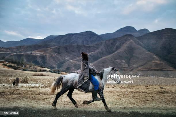 A Basotho horseman rides a horse along the road leading to the Maluti Mountains on July 9 2018