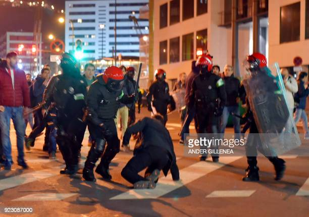 Basque autonomous police officers break up a group of Athletic Bilbao fans outside the San Mames stadium before the Europa League Round of 32 second...