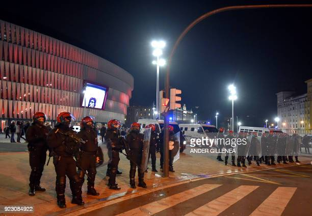 Basque autonomous police officers stand guard outside the San Mames stadium before the Europa League Round of 32 second leg football match between...