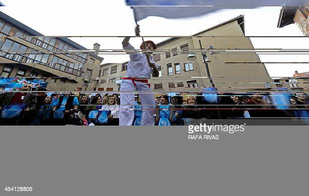 A Basque dancer waves a flag as people brandish posters with a drop forming a big wave during a march called by group Tantaz Tanta Itsasoa Gara and...