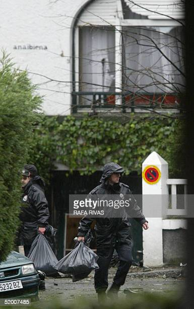 Basque regional policemen clean the area where a car bomb exploded 18 January 2005 at Getxo in the Basque country which armed Basque separatist group...