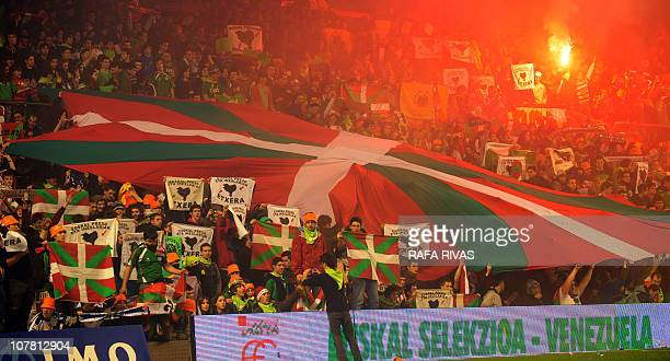 Basque selection team's supporters unfold an Ikurrina during a friendly football match against Venezuela at the San Mames stadium in the Northern...