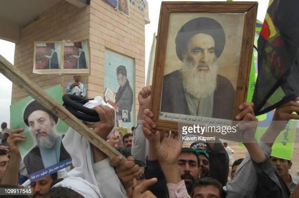 Basra, Iraq, 10th May 2003: Iraqi Shia followers of Ayatollah Mohammad Baqer Hakim, hold his posters and those of Ayatollah Ali al-Sistani, while...