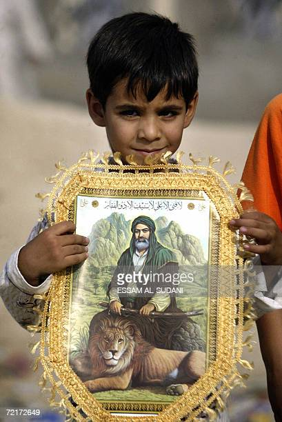 An Iraqi Shiite boy carries a framed picture of Shiite Imam Ali as he heads with his family to the Shiite Shrine 'alKhatwa' believed to be the first...
