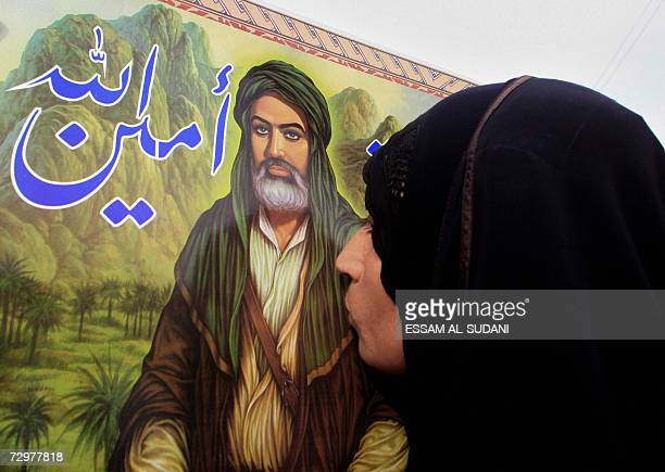 An Iraqi Shiite woman kisses the picture of Shiite Imam Ali as she heads with her family to the Shiite Shrine 'alKhatwa' believed to be the first...