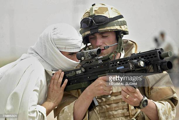 An Iraqi youth looks through the sight of a British soldier's machine gun as he patrols an area in the southern Iraqi city of Basra, 14 April 2007....