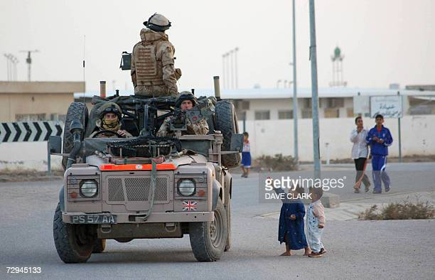 Iraqi children hold out a toy to British soldiers from 63 Squadron of the Royal Air Force Regiment on patrol in the northern suburbs of the southern...