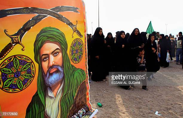 Iraqi Shiites walk past a poster for Shiite Imam Ali as they head to the Shiite Shrine 'alKhatwa' believed to be the first place visited by the late...