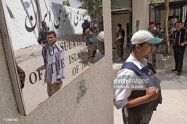 Iraqis are reflected on the silver tainted plate of the new Iranian consulate as an Iraqi policeman guards its entrance during the opening ceremony...