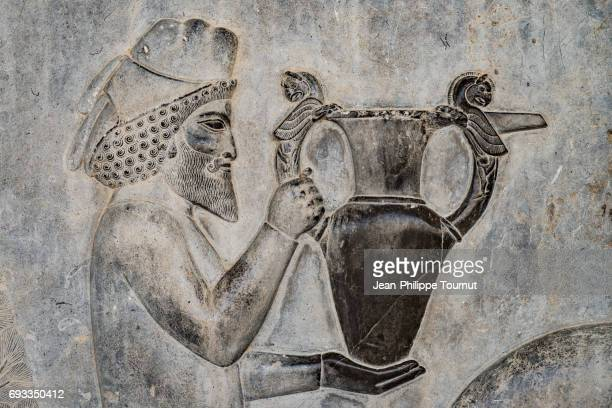 bas-relief from the apadana depicting an armenian bringing their famous wine to the king,  ancient city of persepolis, shiraz, fars province, iran - mesopotamian art stock photos and pictures