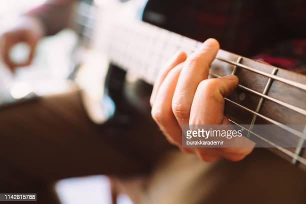 bass guitar player - pizzicare le corde di uno strumento foto e immagini stock
