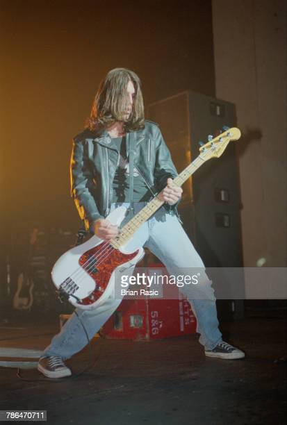 Bass guitarist C J Ramone performs live on stage playing a white Fender Precision Bass guitar with American punk group Ramones at Brixton Academy in...