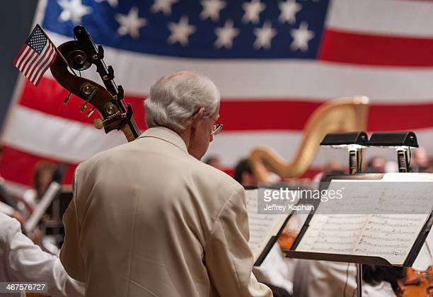 Bass player in the Grand Teton Music Festival symphony. He is seen from the back while reading music and there is a small American flag attached to...